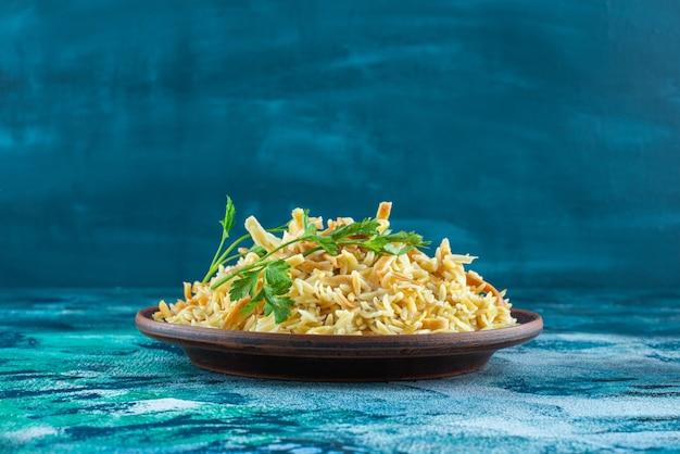 Gustosi noodle fatti in casa in una ciotola, su sfondo blu.
