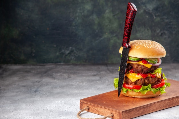 ぼやけた表面の左側にある木製のまな板に自家製のおいしいサンドイッチとフォーク