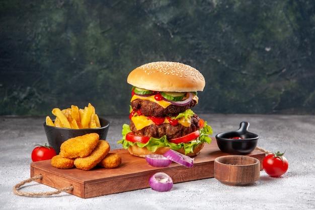 Panino gustoso fatto in casa e pomodori pepite di pollo cipolle pepe su tagliere di legno ketchup patatine fritte su superficie sfocata
