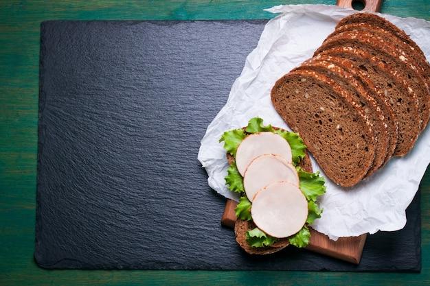 Домашнее вкусный бутерброд с листьями салата и ветчиной на разделочной доске