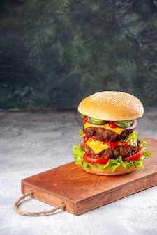 Homemade tasty sandwich on wooden board tied up with rope on blurred surface with free space