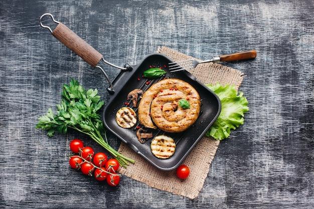 냄비에 건강 한 야채와 함께 만든 맛있는 나선형 구운 소시지