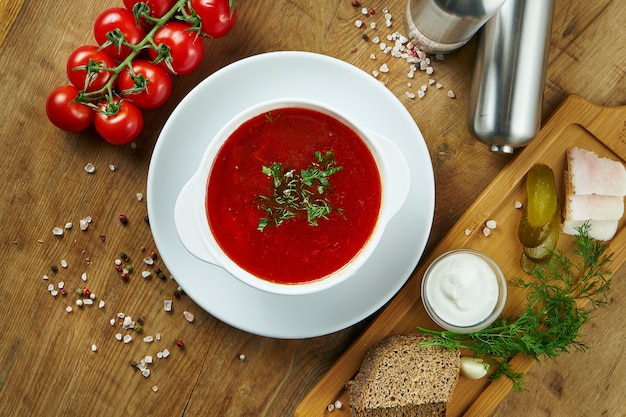 Homemade and tasty ukrainian borsch with sour cream in a bowl on a wooden surface