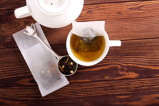 Homemade tea mix in tea bags, over wooden background