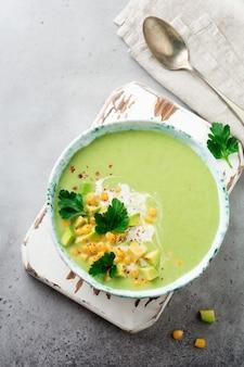 Домашний нежный суп-пюре из авокадо и кукурузы со сливками в деревенской керамической тарелке на сером бетонном старом фоне