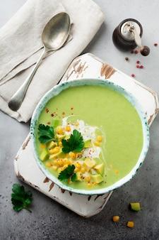 Домашнее нежное суп-пюре из авокадо и кукурузы со сливками в деревенской керамической тарелке на серой бетонной старой поверхности