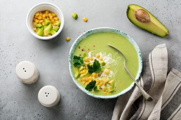 Homemade tender soup puree from avocado and corn with cream in rustic ceramic plate on gray concrete old surface