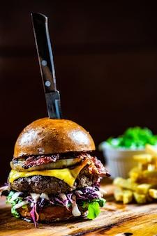 自家製テキサスハンバーガーとベーコンとキャベツのサラダを木の板でお召し上がりいただけます