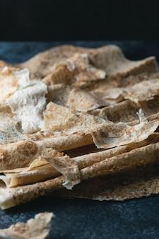 Homemade thin armenian pita bread (lavash) lies on a dark blue stone background. selective focus.