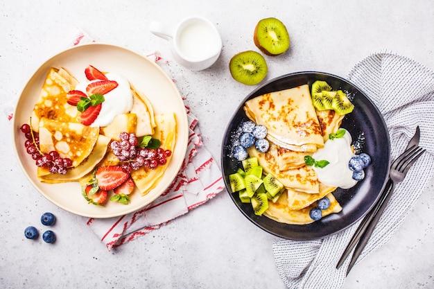 수제 얇은 크레페는 두부 크림, 과일 및 딸기와 함께 흑백 접시에 제공됩니다.