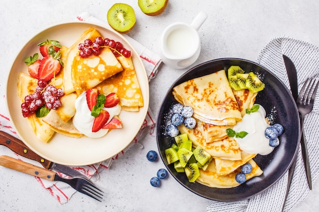 Homemade thin crepes served with curd cream, fruits