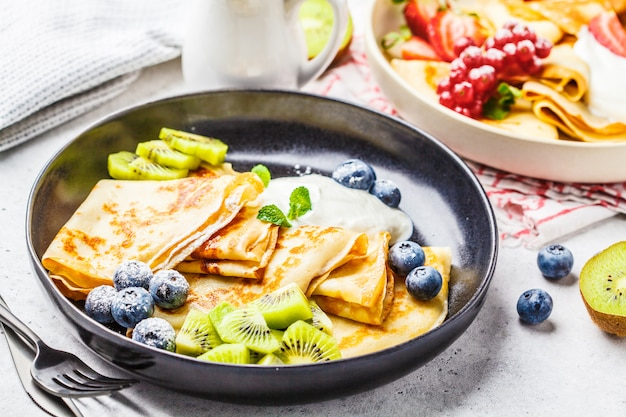 Homemade thin crepes served with curd cream
