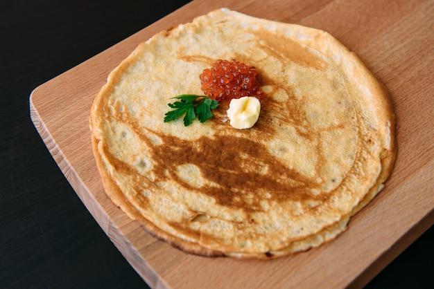 木製のまな板にキャビアと自家製の薄いパンケーキ。