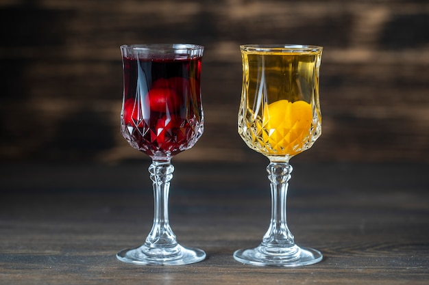 Домашняя настойка красной вишни и желтой алычи в винных бокалах на деревянном фоне