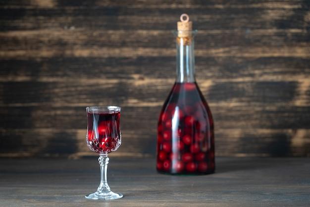 Домашняя настойка красной вишни в стеклянной бутылке и рюмке на деревянном фоне