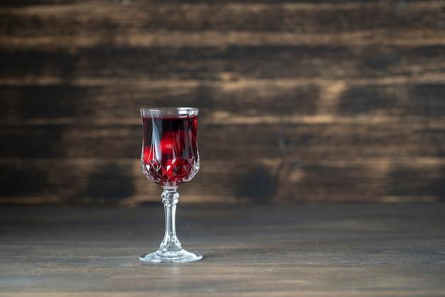 Домашняя настойка красной вишни в бокале для вина на деревянном фоне