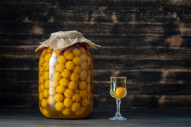 Домашняя настойка желтой алычи в стеклянной банке и винный хрустальный бокал на деревянном фоне