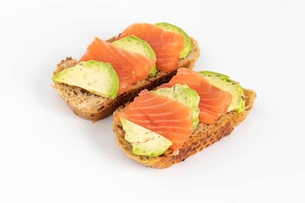 곡물 빵 조각에 연어, 아보카도와 함께 만든 토스트 샌드위치. 건강한 음식.