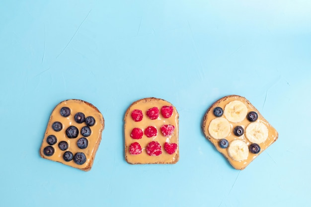 Homemade toast with peanut butter, berries and banana