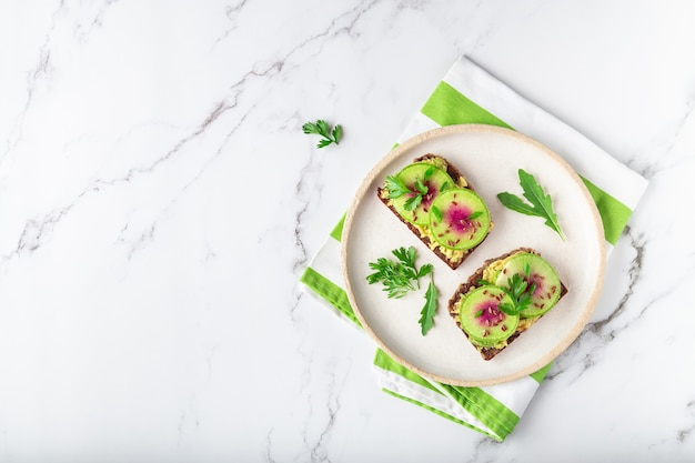 흰색 대리석 배경에 유기농 수박 무 아보카도와 플렉스 씨앗을 곁들인 홈메이드 토스트