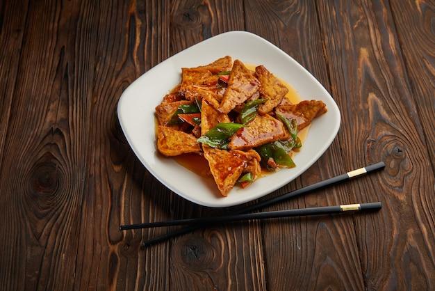 自家製豆腐の炒め物に野菜を温かい甘いソースで炒め、暗い木製のテーブルとコピースペースに箸を置きます。アジア料理コンセプト上面図