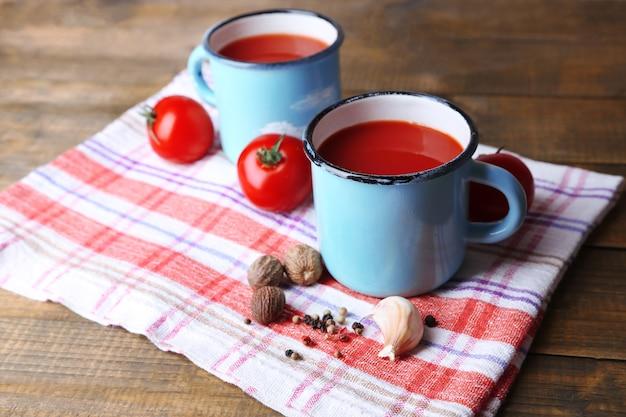 木製の背景に、ナプキンにカラーマグ、スパイス、フレッシュトマトの自家製トマトジュース