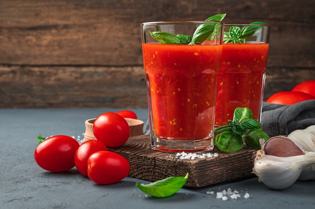 Homemade tomato juice with basil on a wooden background