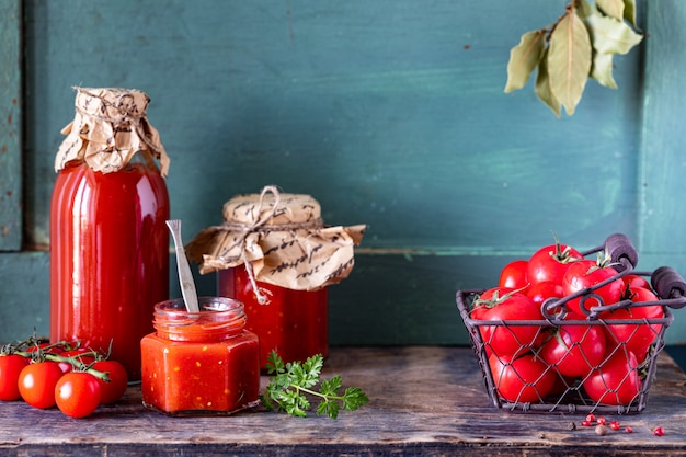 Homemade tomato ketchup made from ripe red tomatoes in glass jars with ingredients on an old wooden table