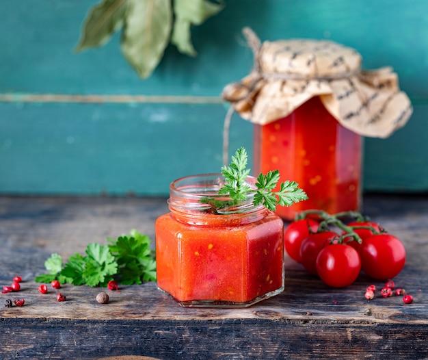 古い木製のテーブルの上に材料を入れたガラスの瓶に熟した赤いトマトから作られた自家製トマトケチャップ。コピースペース