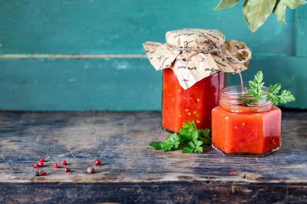 Домашний томатный кетчуп из спелых красных помидоров в стеклянных банках с ингредиентами на старом деревянном столе. копировать пространство