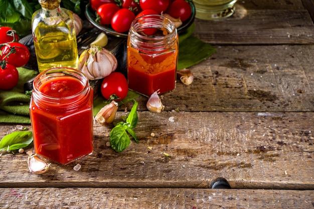 바질, 마늘, 신선한 토마토를 곁들인 홈메이드 토마토 소스. 케첩, 작은 항아리에 마리나라 소스. 신선한 야채와 바질을 곁들인 나무 배경.
