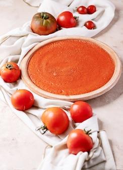 Домашний томатный суп со свежими био-помидорами и хлебом на белом фоне текстуры. вид сверху, плоская планировка. копировать пространство