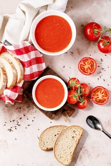 Homemade tomato soup served with fresh bio tomatoes and bread over white texture background. top view, flat lay. copy space