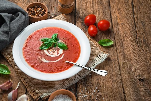 木製の背景にバジルとクリームの自家製トマトスープ健康的な有機食品
