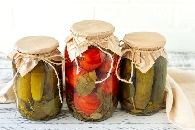 집에서 만든 토마토와 오이는 나무 배경에 있는 유리병에 보관합니다.