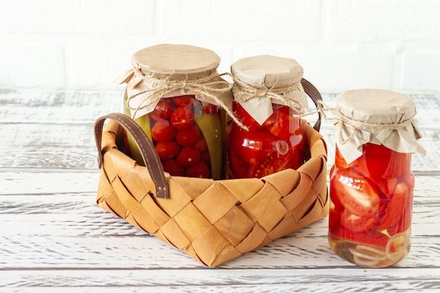 집에서 만든 토마토는 나무 배경에 있는 흰색 고리버들 바구니에 담긴 유리병에 보관합니다.