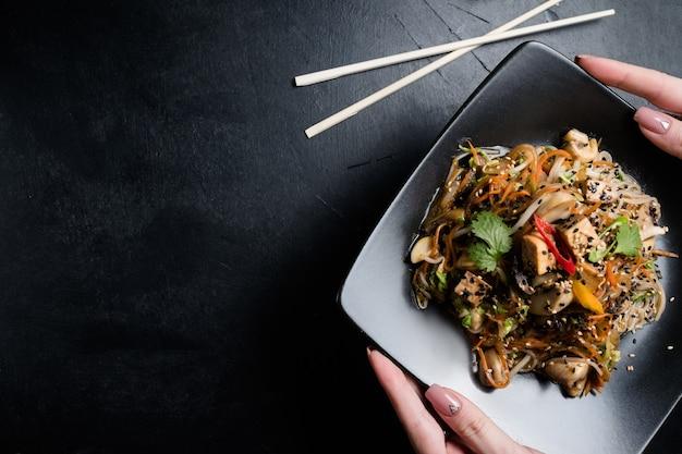 Домашние традиционные азиатские блюда. женщина, держащая тарелку с лапшой овощной жареный салат тофу.