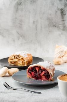 自家製の伝統的なオーストリアのリンゴのシュトルーデル、新鮮なリンゴ、ナッツ、粉砂糖。カフェのメニュー。黒い皿にケーキ、白い大理石の背景に白いカップ。縦の写真。