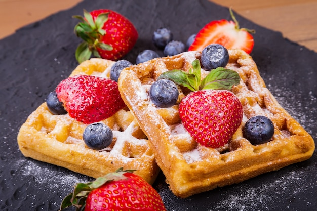 Homemade traditional belgian waffles with fresh fruit, berries and sugar powder on black plate. flat lay,