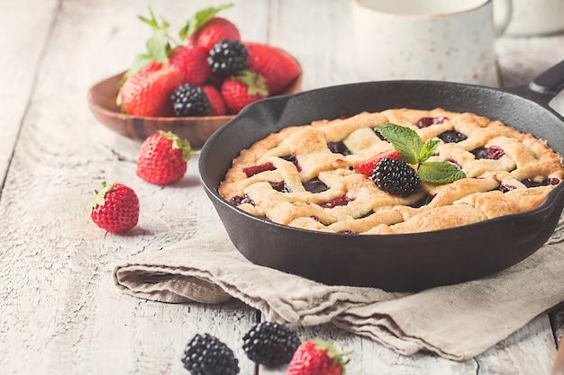 Домашний традиционный ягодный пирог на сковороде, сладкая выпечка на белом деревенском деревянном столе