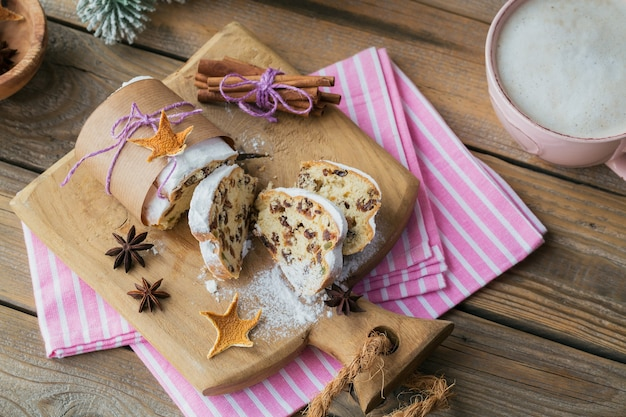 Homemade traditional christmas dessert stollen with dried berries, nuts and powdered sugar on top stands on rustic wooden table with cup of coffee and fir tree branches