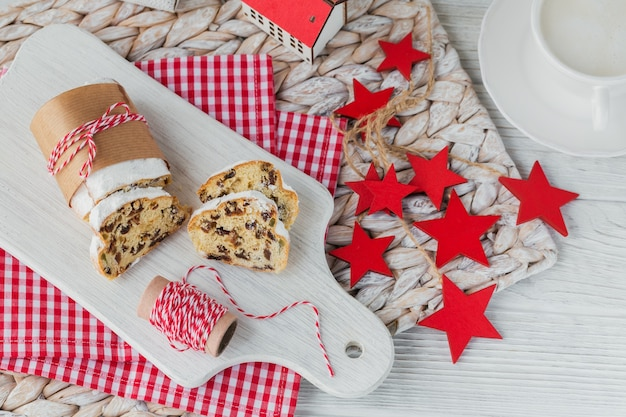 Homemade traditional christmas dessert stollen with dried berries, nuts and powdered sugar on top stands on white rustic wooden table with cup of coffee.