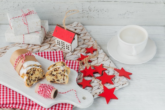 Homemade traditional christmas dessert stollen with dried berries, nuts and powdered sugar on top stands on white rustic wooden table