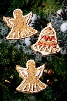 華やかなアイシングで自家製の伝統的なクリスマスジンジャーブレッドクッキー。クリスマスの装飾とモミの木とジンジャーブレッドの天使と鐘