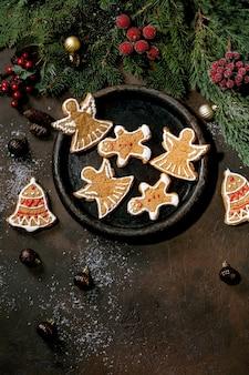 華やかなアイシングで自家製の伝統的なクリスマスジンジャーブレッドクッキー。ジンジャーブレッドマン、天使、クリスマスの装飾が施されたセラミックプレートの鐘。フラットレイ