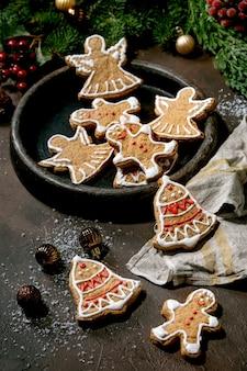 華やかなアイシングで自家製の伝統的なクリスマスジンジャーブレッドクッキー。ジンジャーブレッドマン、天使、クリスマスの装飾が施されたセラミックプレートの鐘。