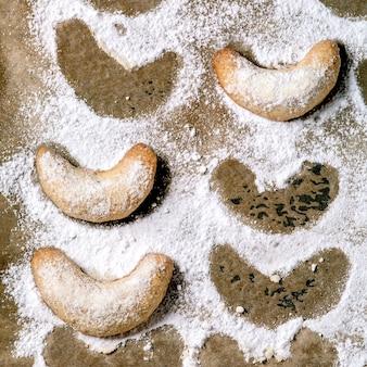 Домашнее традиционное рождественское песочное печенье ванильные полумесяцы с сахарной пудрой на бумаге для выпечки. вид сверху. квадратное изображение