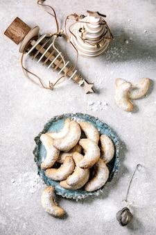 Домашнее традиционное рождественское песочное печенье ванильные полумесяцы с сахарной пудрой. на керамической тарелке с деревянными рождественскими украшениями на светло-серой поверхности.