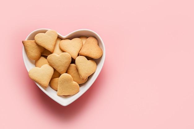 Домашнее традиционное печенье в форме сердца на день святого валентина на розовом