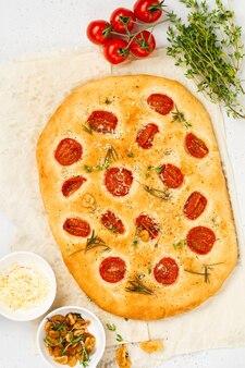 Домашняя традиционная итальянская выпечка хлеба с помидорами черри, пармезаном и розмарином на деревенской светлой стене стола. вид сверху.